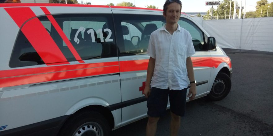 Hermino Katzenstein vorm Fahrzeug des DRK