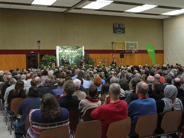 Foto: Mit 450 Menschen gefüllte Halle in Meckesheim, im Hintergund die Bühne