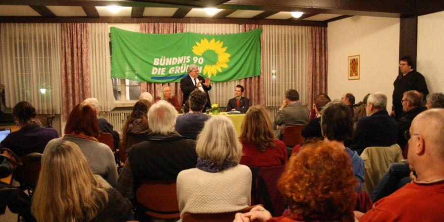Foto: Reinhard Bütikofer refeiert vor den Gästen, neben ihm Hermino KAtzenstein und Rolf Gramm