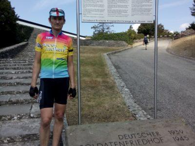 Hermino Katzenstein in Fahrradbkleidung vor der Schautafel zum Soldatenfriedhof auf dem Futa-Pass