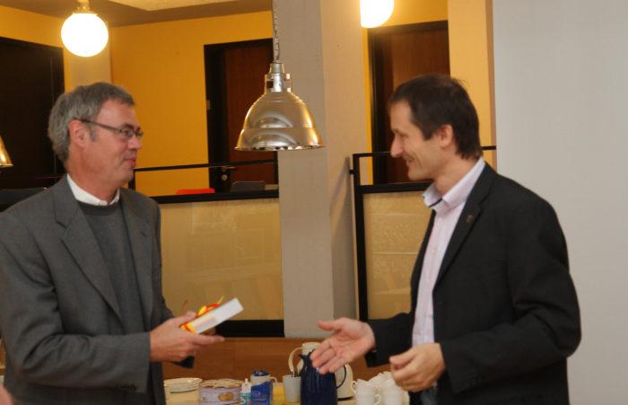 Hermino Katzenstein schenkt Rainer Drös ein Bestimmungsbuch.