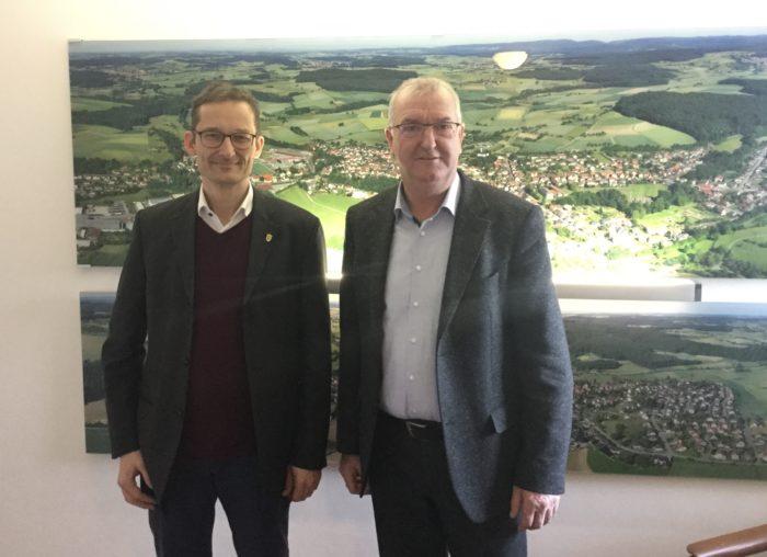Foto des Landtagsabgeordneten Hermino Katzenstein unde des Bürgermeisters wolfgang Jürriens im Rathaus Helmstadt-Bargen; an der wand im Hintergrund sind Luftbilder des Ortes zu sehen