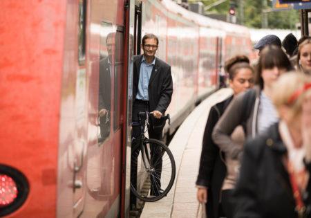 Foto von Hermino Katzenstein, wie er aus einer S-Bahn aussteigt (und sein Fahrrad dabei hat)