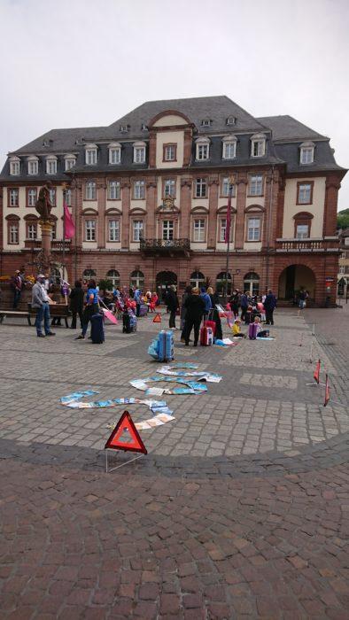 Blick über die Demo zum Heidelberger Rathaus, im Vordergrund auf dem Boden ein aus Katalogen gelegtes SOS