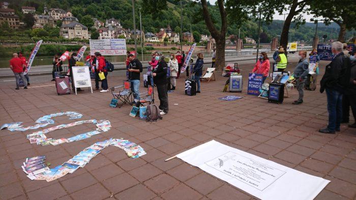 Blick über die Demo am Neckarmünzplatz in Heidelberg, im Vordergrund auf dem Boden ein aus Katalogen gelegtes SOS