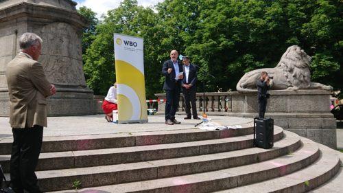 Verkehrsminister Hermann bei seiner Rede, hinter ihm ein RollUp des WBO, links vorner WBO-Präsident Sedelmaier